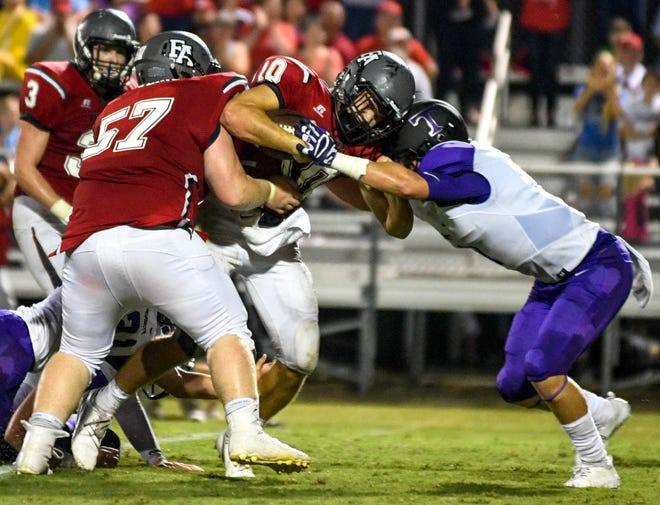 TCA's Harrison Freeman (15) tries to hold back Fayette's Rube Scott Rhea (10) as Rhea moves down the field in a TSSAA football game between Trinity Christian Academy at Fayette Academy in Somerville, Tenn., on Thursday, Aug. 23, 2018.