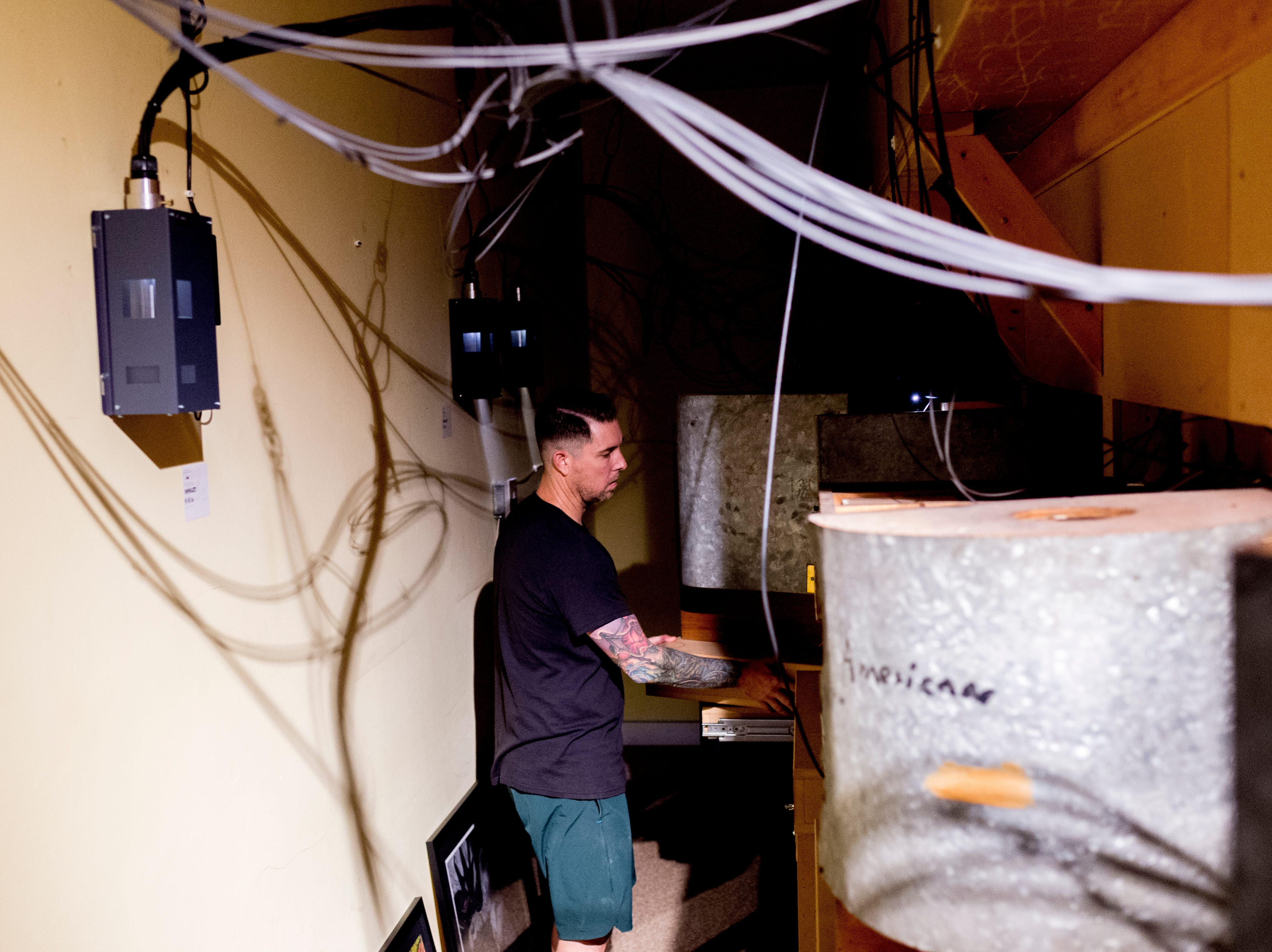 Robmat Butler, preparator at the Knoxville Museum of Art, works in the crawlspace behind the exhibit in the Thorne Room in Knoxville, Tennessee on Tuesday, August 21, 2018. The nine miniature rooms were created in the 1930s and 40s by Narcissa Niblack Thorne to a scale of one inch to one foot.