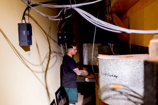 Robmat Butler, preparator at the Knoxville Museum of Art, works in the crawlspace behind the exhibit in The Thorne Rooms on Aug. 21. The nine miniature rooms were created in the 1930s and '40s by Narcissa Niblack Thorne to a scale of 1 inch to 1 foot.