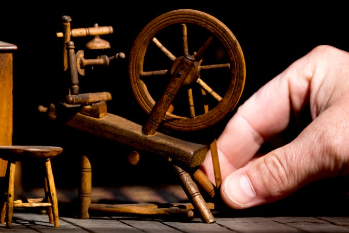 Robmat Butler, preparator at the Knoxville Museum of Art, adjusts the spinning wheel inside the Early American Kitchen display in the Thorne Room at the Knoxville Museum of Art in Knoxville, Tennessee on Tuesday, August 21, 2018. The nine miniature rooms were created in the 1930s and 40s by Narcissa Niblack Thorne to a scale of one inch to one foot.