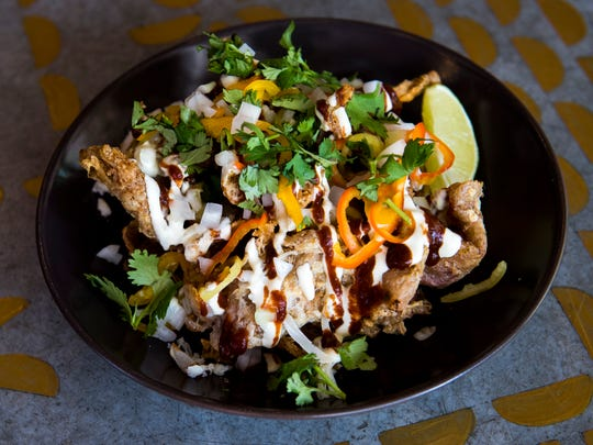 """The """"Nachos"""" at Tako Taco are made with crispy chicken skin, chili spices, Sweetwater cheese blend, pickled peppers, avocado crema, chipotle puree, onions and and cilantro."""