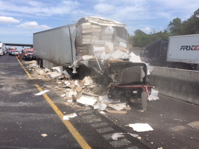 Crews removed a truck that crashed into a median wall during a two-tractor trailer crash on Interstate 40. The crash backed up traffic for several miles.