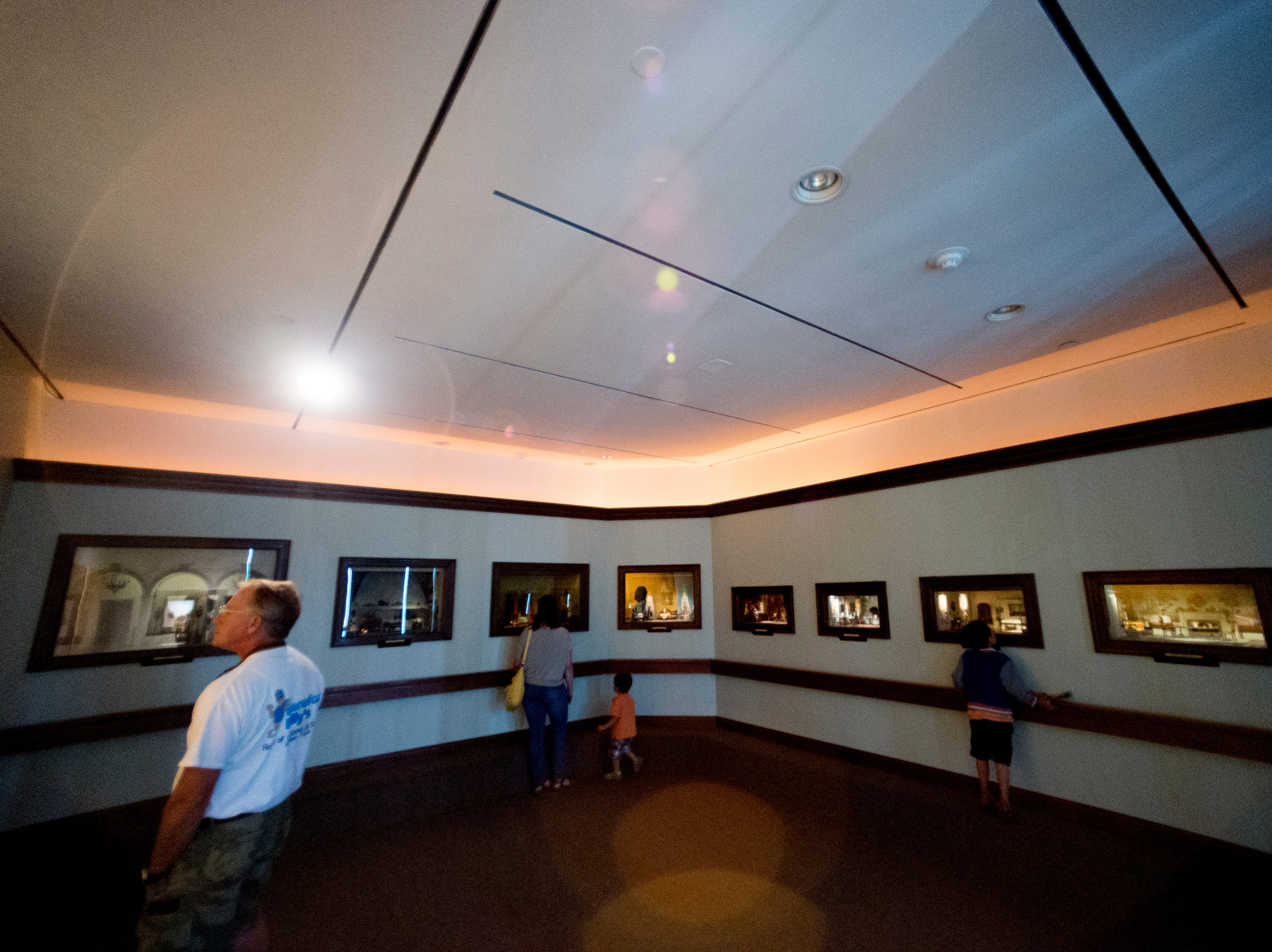 Visitors look at displays in the Thorne Room at the Knoxville Museum of Art in Knoxville, Tennessee on Tuesday, August 21, 2018. The nine miniature rooms were created in the 1930s and 40s by Mrs. James Ward Thorne to a scale of one inch to one foot.