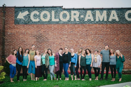 """Teachers and staff of The Glowing Body yoga studio gather in 2017 beneath the """"Color-Ama"""" company logo, left over from the days when the building warehoused prefabricated aluminum. Shown are co-owner Kim Lomonaco, Veronica Carmazzi, Jen Schappel, Ben Willis-Becker, Jill Frere, Gina Baker, Amberly Kelley, Jessica Dalton-Carriger, Cheryl Maslar, Allison Bradley, Rebecca Simmons, Meagan Egli, Cristina McClure, Barbara Steppe, Colby Simmons, Claire Hyrka and co-owner Kelly Scott. Dec. 4, 2017."""
