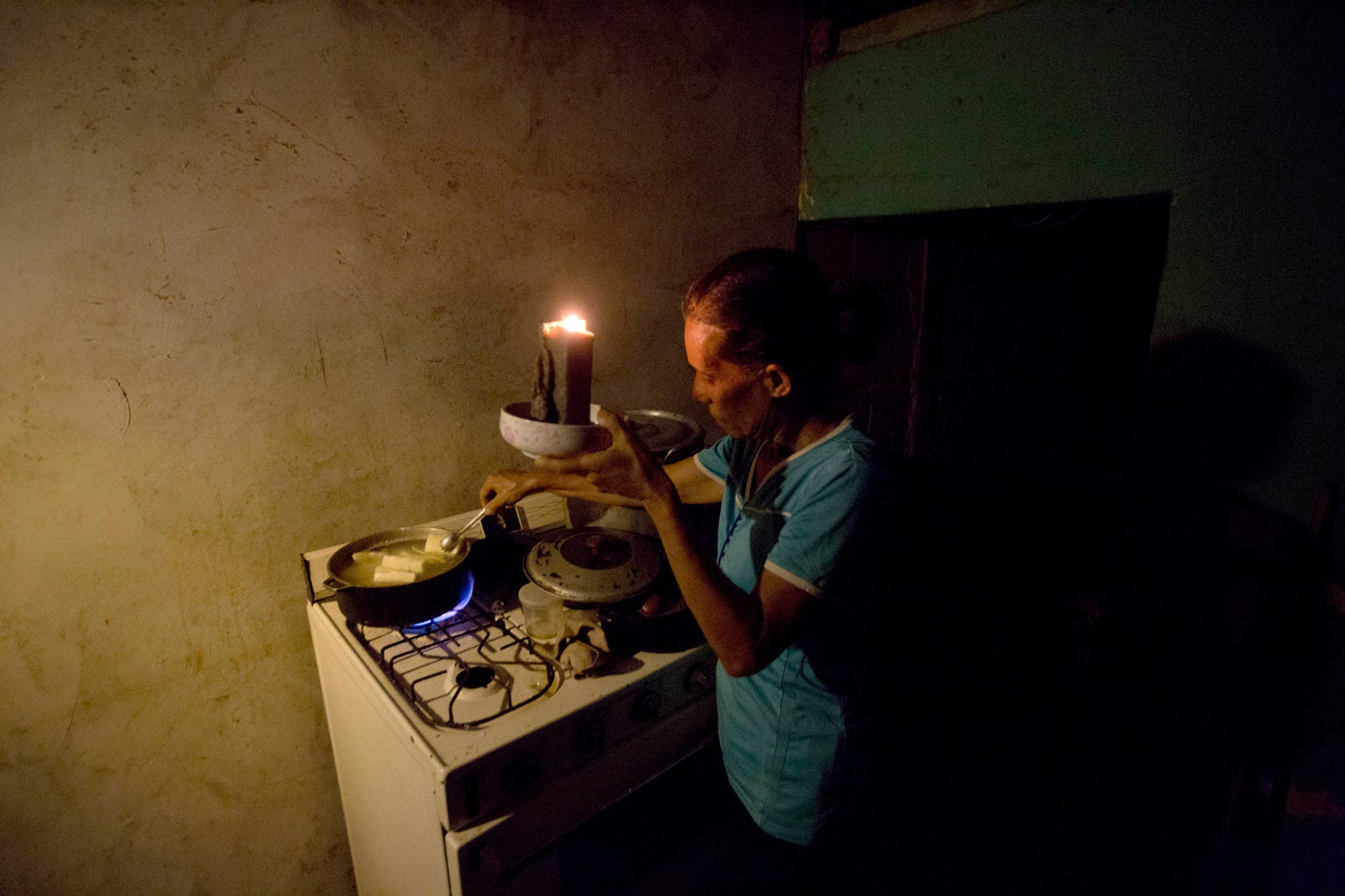 "In this Aug. 19, 2018 photo, Mireya Marquez uses candlelight to cook her dinner of boiled ""cassava,"" also known as yuca and manioc, during a blackout in Maracaibo, Venezuela. For months Maracaibo's residents have endured rolling blackouts, but things turned dire on August 10 when a fire destroyed a main power line supplying the city of 1.5 million people. (AP Photo/Fernando Llano)"