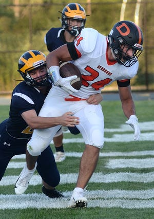 Hartland's Aidan Ross tackles Dearborn's Tarek Silmi in the end zone for a safety on Thursday, Aug. 23, 2018.