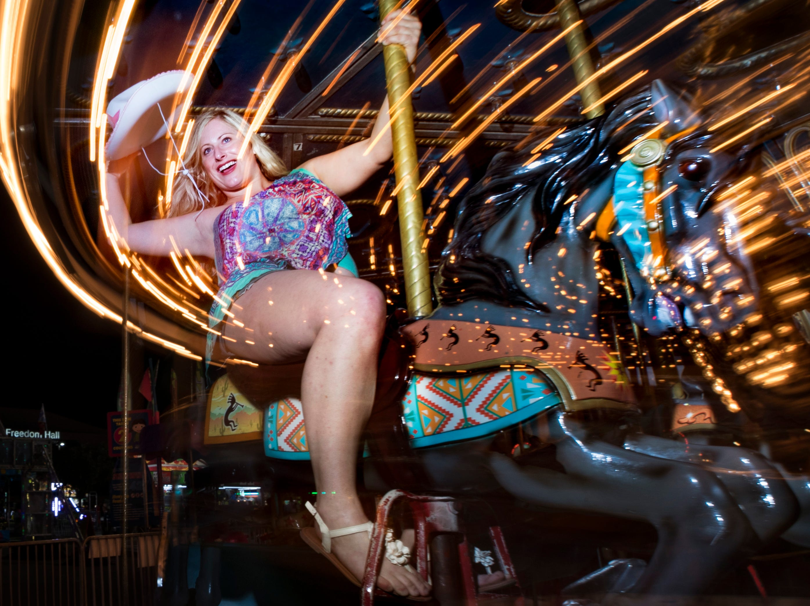 "Pearl Hagadorn has some fun on the carousel at the Kentucky State Fair midway on Thursday evening. ""I actually have to go race horses at the track in the morning,"" Hagadorn said. Aug. 24, 2018"