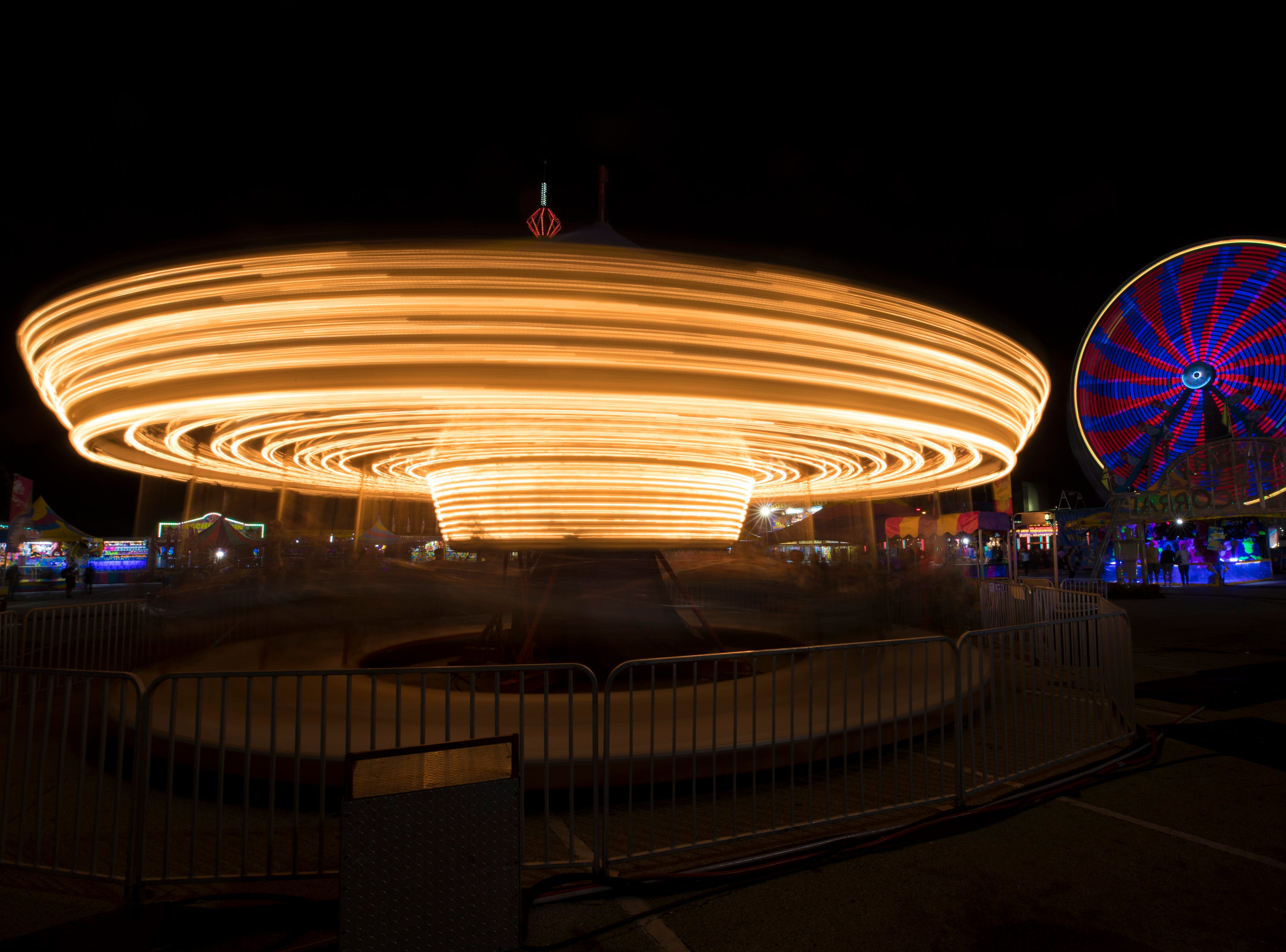 The carousel and ferris wheel at the Kentucky State Fair midway on Thursday evening. Aug. 24, 2018