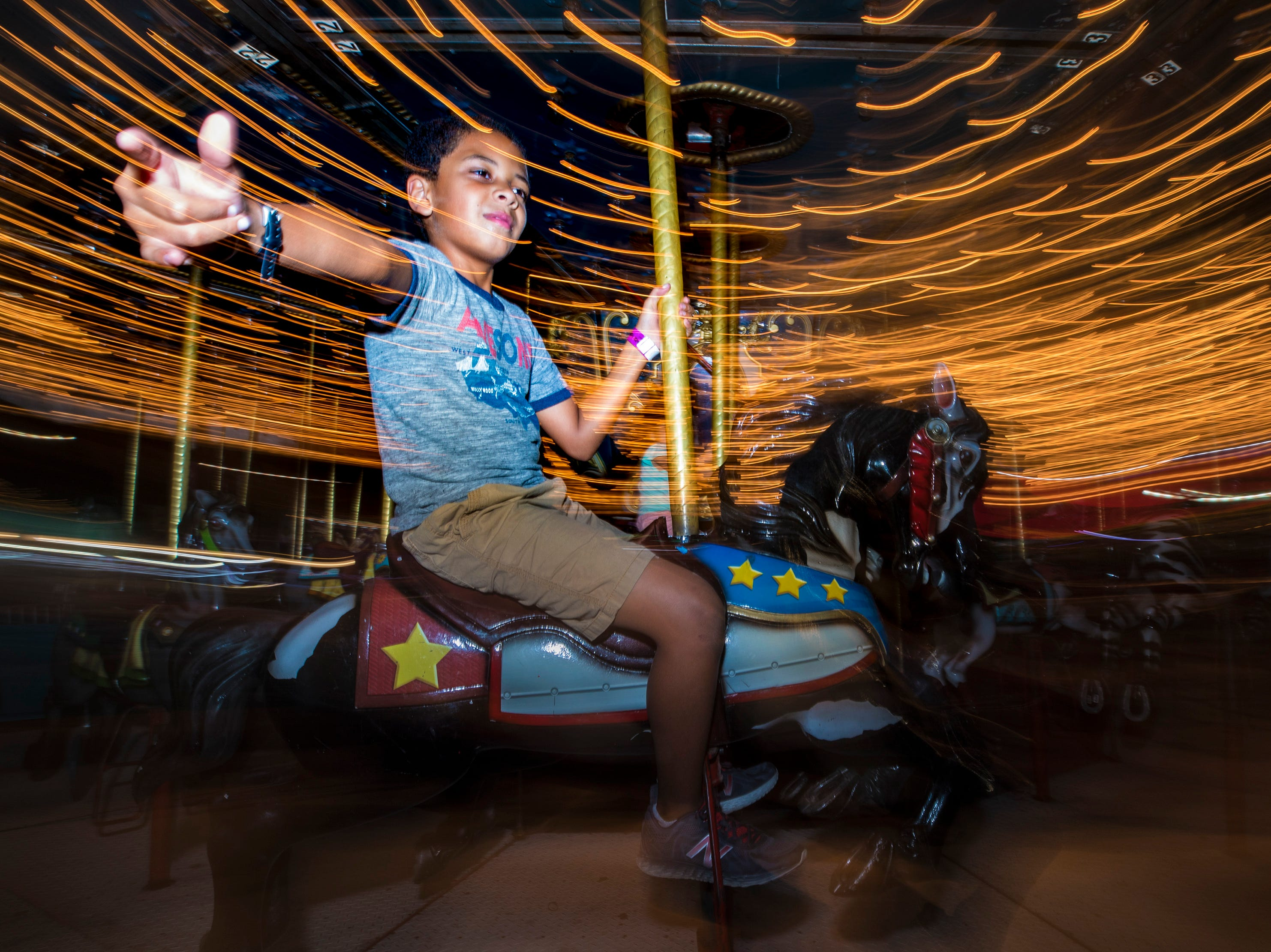 Noah Ransom, 9, rides the carousel at the Kentucky State Fair on Thursday evening. Aug. 24, 2018