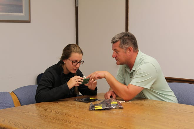 Craig Oliver, a Williams International team leader of infrastructure and facilities, explains the intricacies of a circuit board that helps expand student skills in diagnosing, troubleshooting and maintaining manufacturing machinery in his role as a mentor to Emily Eggart, a Michigan Advanced Technician Training (MAT2) student and Williams apprentice.