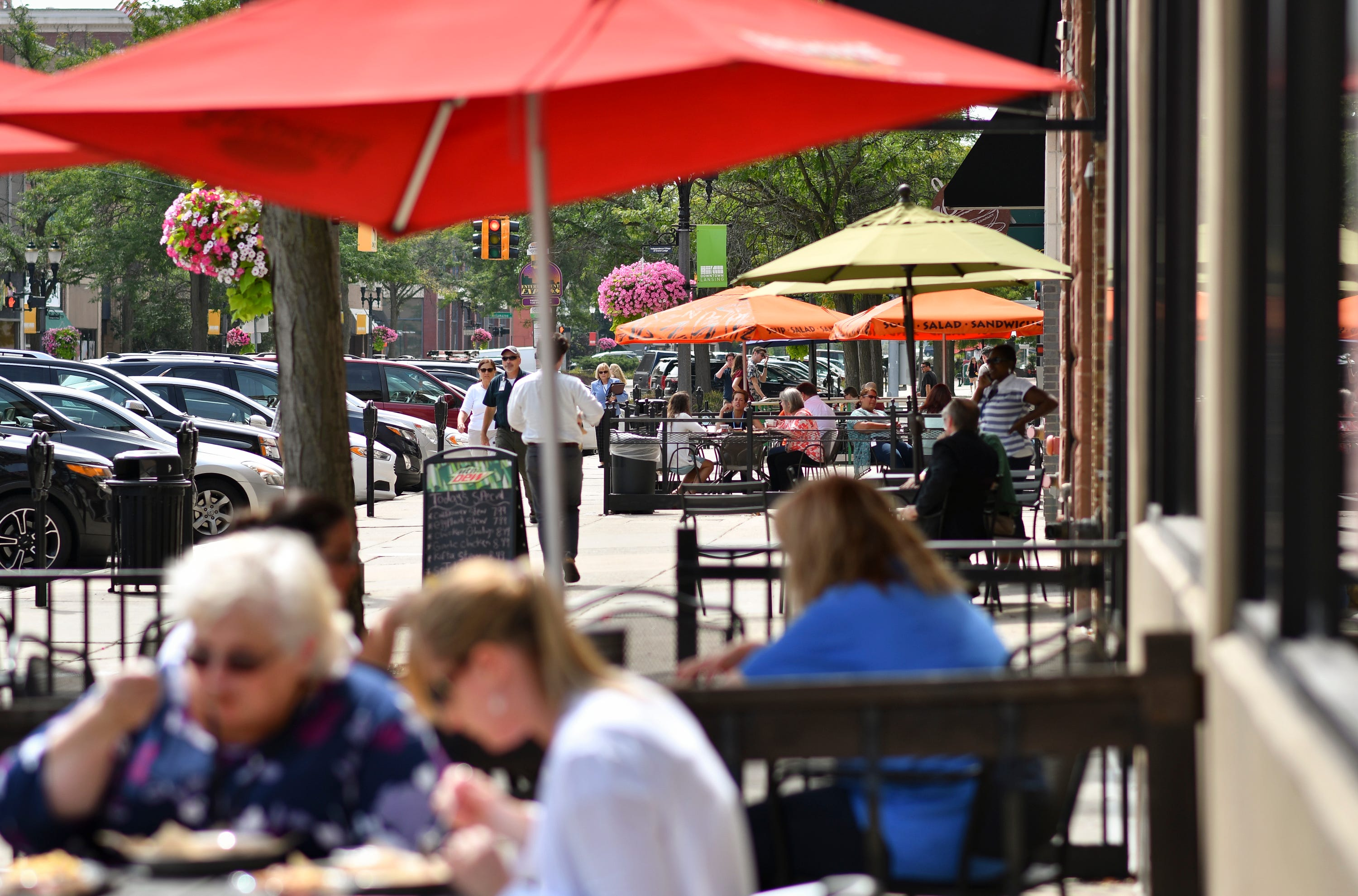 People eat outdoors during the lunch hour Friday, Aug. 24, 2018, in downtown Lansing on S. Washington Square.