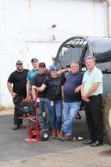 MAT2 apprentice Emily Eggart (center) takes a break from heavy maintenance work on material handling equipment with her Williams International colleagues. Pictured from left are Matthew Truax, Bradley Schaeffer, Jason Rutten, Eggart, David Curl and Craig Oliver.