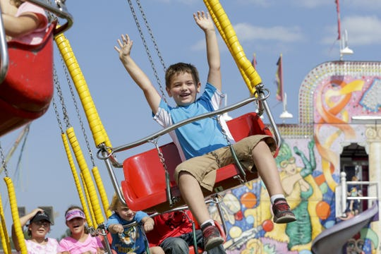 Eli Micke, 6, of Brillion reacts on a swing ride at the Manitowoc County Fair on Aug.  23, 2018, in Manitowoc.
