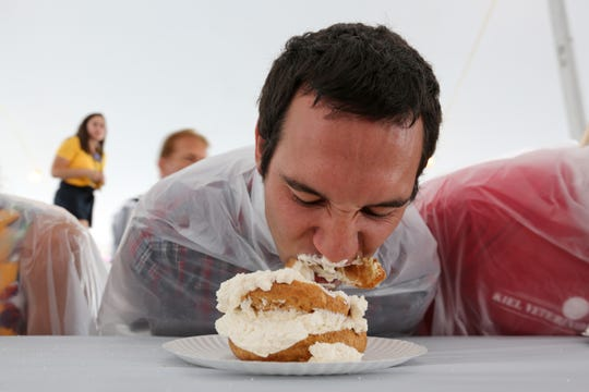 Dr. Joe Herring, of Veterinary Associates, digs into his cream puff during the eating contest at the Manitowoc County Fair Thursday, Aug. 23, 2018, in Manitowoc.