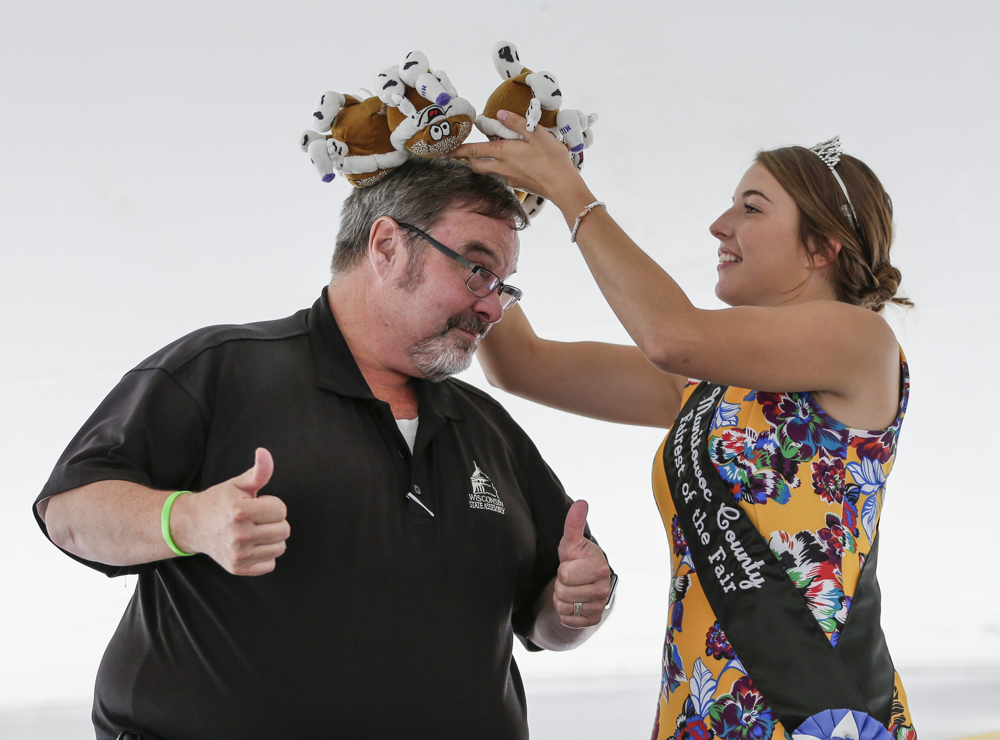 Emily Hutterer, Manitowoc County's Fairest of the Fair, crowns State Rep. Paul Tittl champion of the cream puff eating contest at the Manitowoc County Fair Thursday, Aug. 23, 2018, in Manitowoc.
