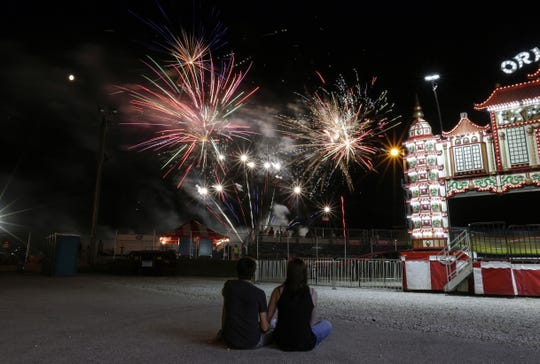 Max Schoett, 16, and Olivia Lutterman, 17, of Manitowoc watch the fireworks go off next to a nearly full moon at the Manitowoc County Fair Wednesday, Aug. 22, 2018.
