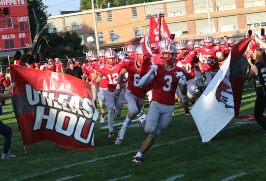 Shelby's Uriah Schwemley goes through the banner during the season opener against Madson on Thursday.