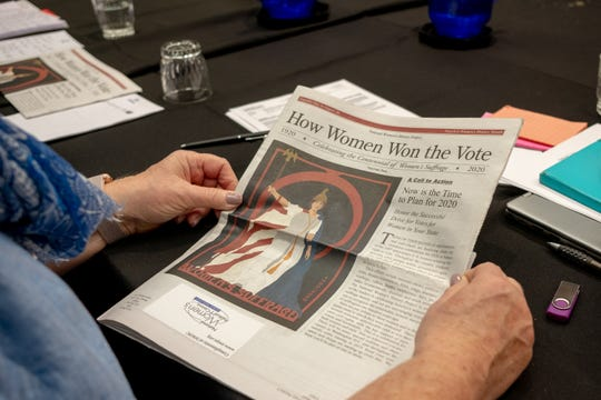 Donna Lent holds a publication discussing recent political victories won by women across the country at the annual meeting of the National Women's Political Caucus.