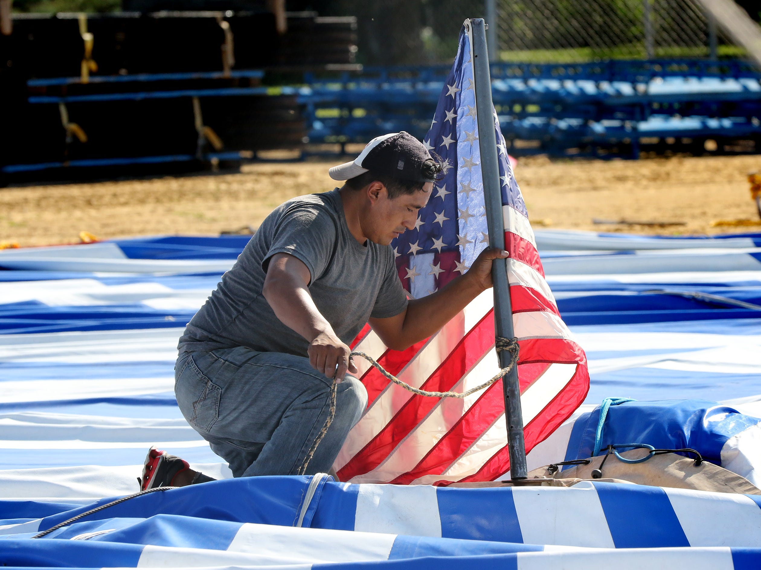 A Culpepper and Merriweather Circus roustabout places a flag that will top one of two main poles for the big top tent. The Circus arrived in Dousman on Aug. 23 for two performances. While setup of the big top takes three hours, it can be taken down and packed onto two trucks in 90 minutes.