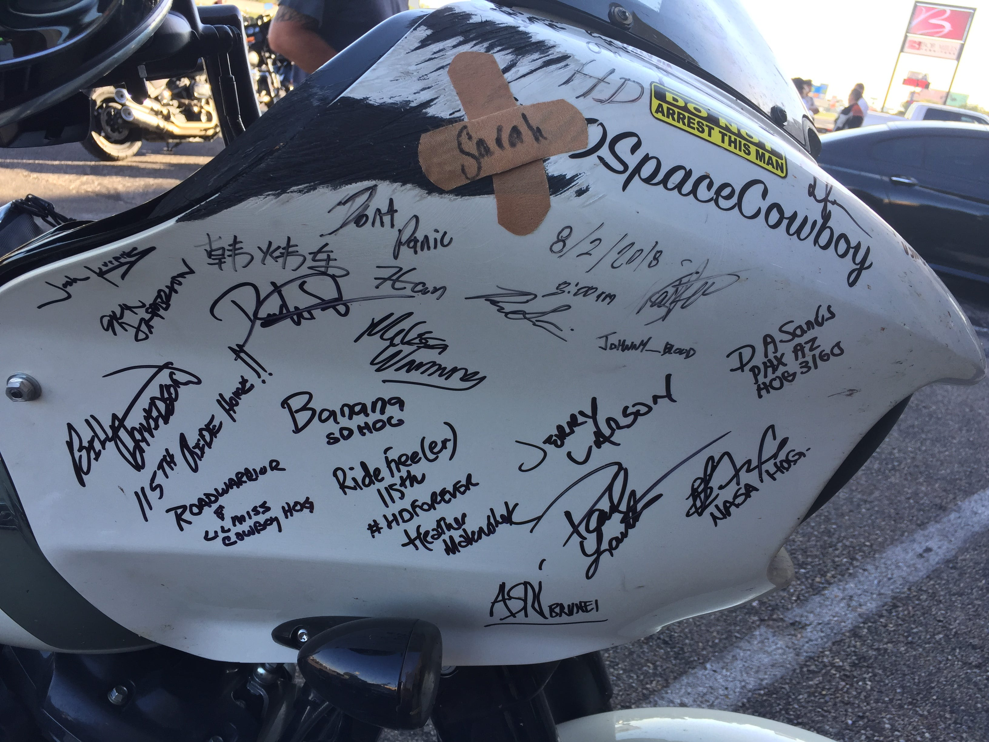 Signature of riders cover the gas tank of a motorcycle.