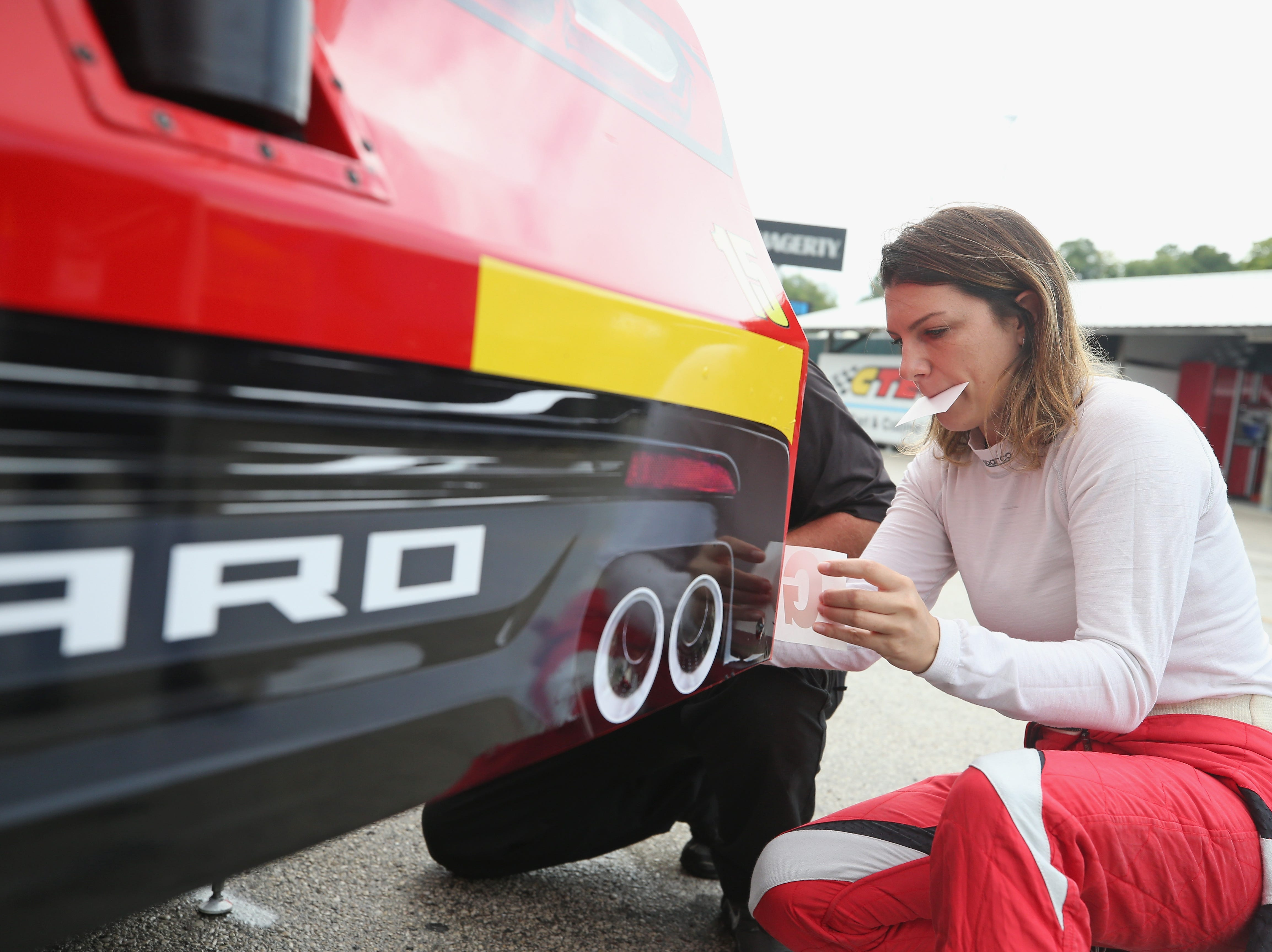 ELKHART LAKE, WI - AUGUST 24:  Katherine Legge, driver of the #15 Airtec Chevrolet, applies decals to her car during practice for the NASCAR Xfinity Series Johnsonville 180 at Road America on August 24, 2018 in Elkhart Lake, Wisconsin.  (Photo by Matt Sullivan/Getty Images)
