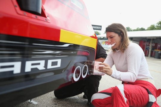 Katherine Legge applies decals to her car Friday during practice for the NASCAR Xfinity Series Johnsonville 180 at Road America.
