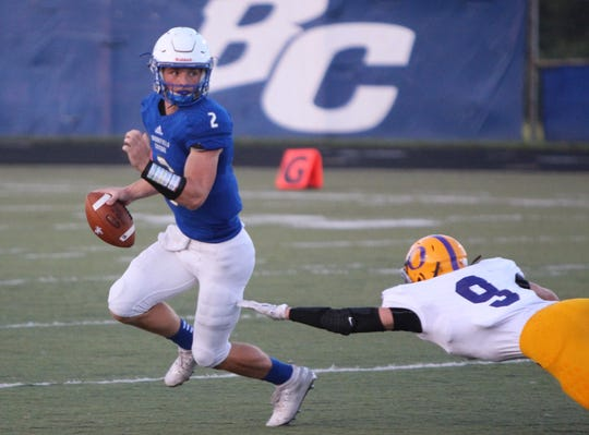 Brookfield Central quarterback Drew Leszczynski escapes Oconomowoc linebacker Rome Zupke on August 23.