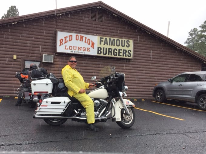 "Ted Poston, 58, a general contractor from Los Angeles, put on his rain gear in Overgaard, Arizona. Rain steadily pounded for about a half-hour. Poston was the only rider on the trip who didn't wear a helmet, which is not required by Arizona or New Mexico law. ""To me, this is total freedom,"" he said."
