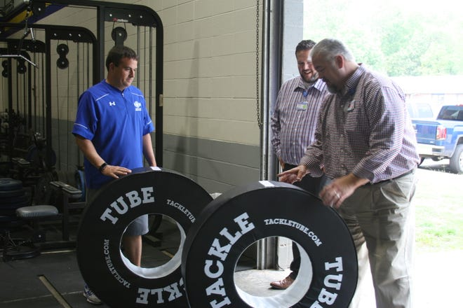 Mountain Home Coach Bryan Mattox (far left) receives two Tackle Tubes donated by Baxter Regional Medical Center. The tubes, presented by BRMC Director of Marketing Tobias Pugsley and Market Analysis and Development Director Mike Beam, are designed to teach those in tackle sports better body positioning to reduce head and neck injuries.