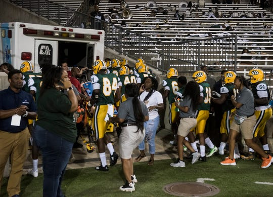 Jeff Davis players run toward the locker room after gunshots were heard outside ASU Stadium in Montgomery, Ala., on Thursday, Aug. 23, 2018. A shooting outside the stadium ended the game with 11 minutes left in the fourth quarter Carver winning 19-3.