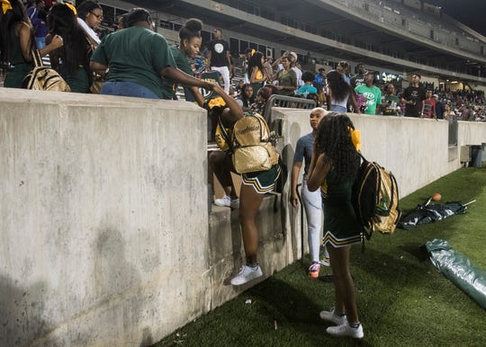 Jeff Davis cheerleaders are helped off the field at ASU Stadium in Montgomery, Ala., on Thursday, Aug. 23, 2018. A shooting outside the stadium ended the game with 11 minutes left in the fourth quarter Carver winning 19-3.
