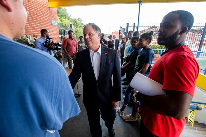 Senator Doug Jones greets volunteers as he visits the site of the Booker T. Washington Magnet High School fire in Montgomery, Ala., on Friday August 24, 2018.