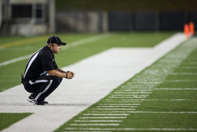 An official waits on the field moments after gun shots were heard nearby at ASU Stadium in Montgomery, Ala., on Thursday, Aug. 23, 2018. A shooting outside the stadium ended the game with 11 minutes left in the fourth quarter Carver winning 19-3 over Jeff Davis.