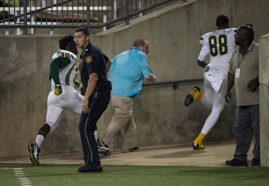 Carver players run toward the locker room after gun shots were heard nearby at ASU Stadium in Montgomery, Ala., on Thursday, Aug. 23, 2018. A shooting outside the stadium ended the game with 11 minutes left in the fourth quarter Carver winning 19-3.