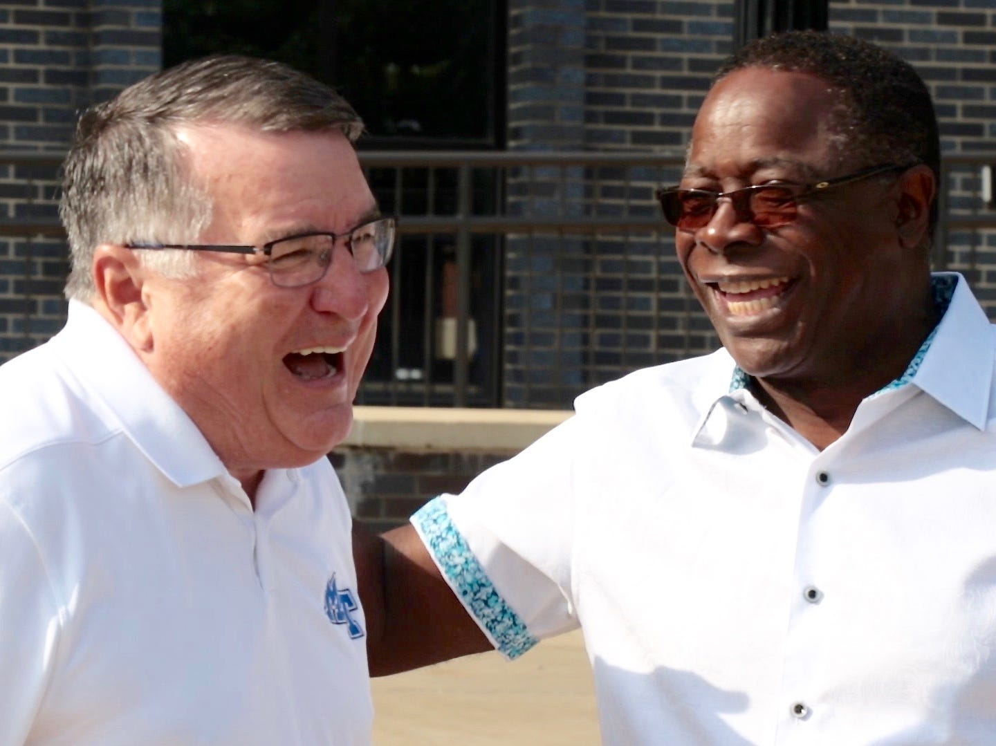 MTSU Women's Basketball Head Coach Rick Insell, left, shares a laugh with President Sidney A. McPhee during Friday's We-Haul efforts to welcome incoming students to campus.
