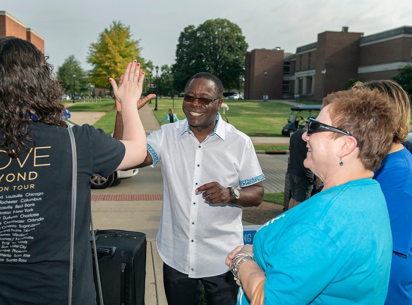 MTSU President Sidney A. McPhee, center, hi-fives freshman Jessica Nasca, left, while her mother, Beverly, right, watches, during the We-Haul move-in outside Corlew Hall on Friday, Aug. 24. Classes for fall semester begin Monday, Aug. 27.