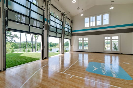 The home has a basketball court complete with scoreboard and timer. Garage doors open to extend the gym space onto the courtyard.