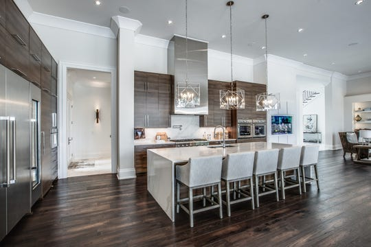 The home's kitchen features top-of-the-line chef-quality appliances, a massive 12-foot island topped with quartz and a hidden walk-in pantry.
