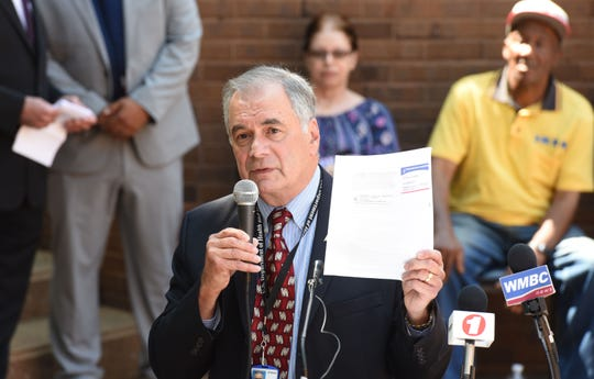 HHS Regional Director Anthony Ferreri holds updated Medicare card which will now have a random identification number in place of the individual's Social Security number.