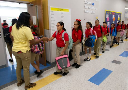 Sixth-grade teacher Sheena Gomez welcomes students to her class at the IDEA Edgemere public school on its second week of operation in east El Paso on Monday, Aug. 20, 2018.