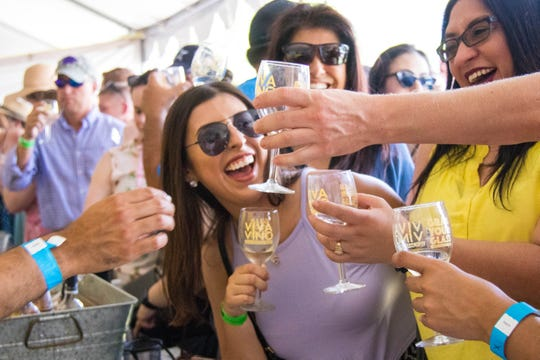 Attendees at the Harvest Wine Festival wait in line for their glasses to be filled with samples of wine.