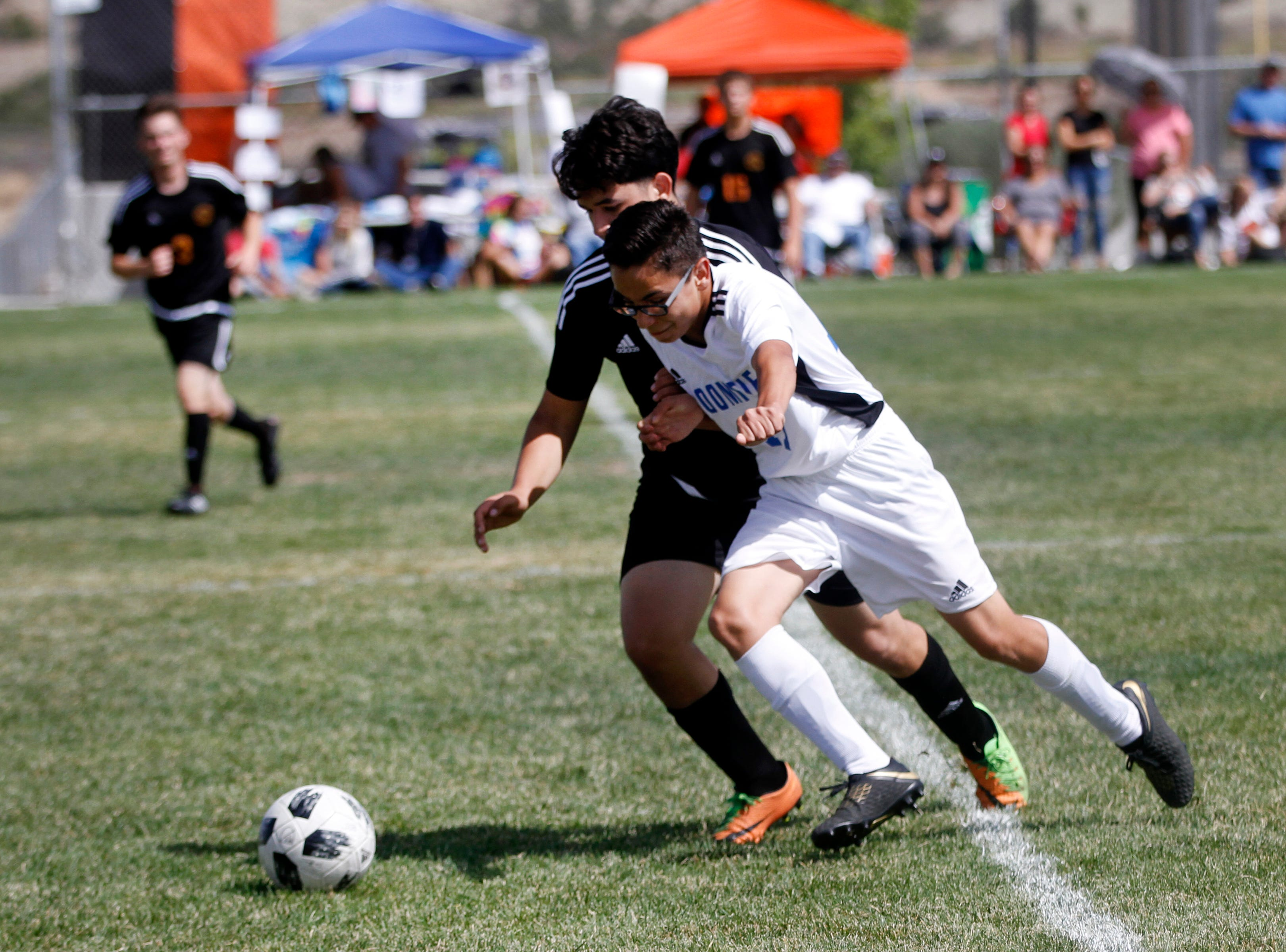 Bloomfield's Rubio Daniel and Aztec's Anthony Aviles battle for the ball, Friday, Aug. 24, 2018 at the Aztec Tiger Soccer Complex.