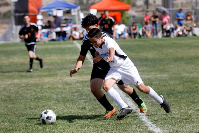 Bloomfield's Rubio Daniel and Aztec's Anthony Aviles battle for the ball during Friday's match at the Aztec Tiger Soccer Complex.