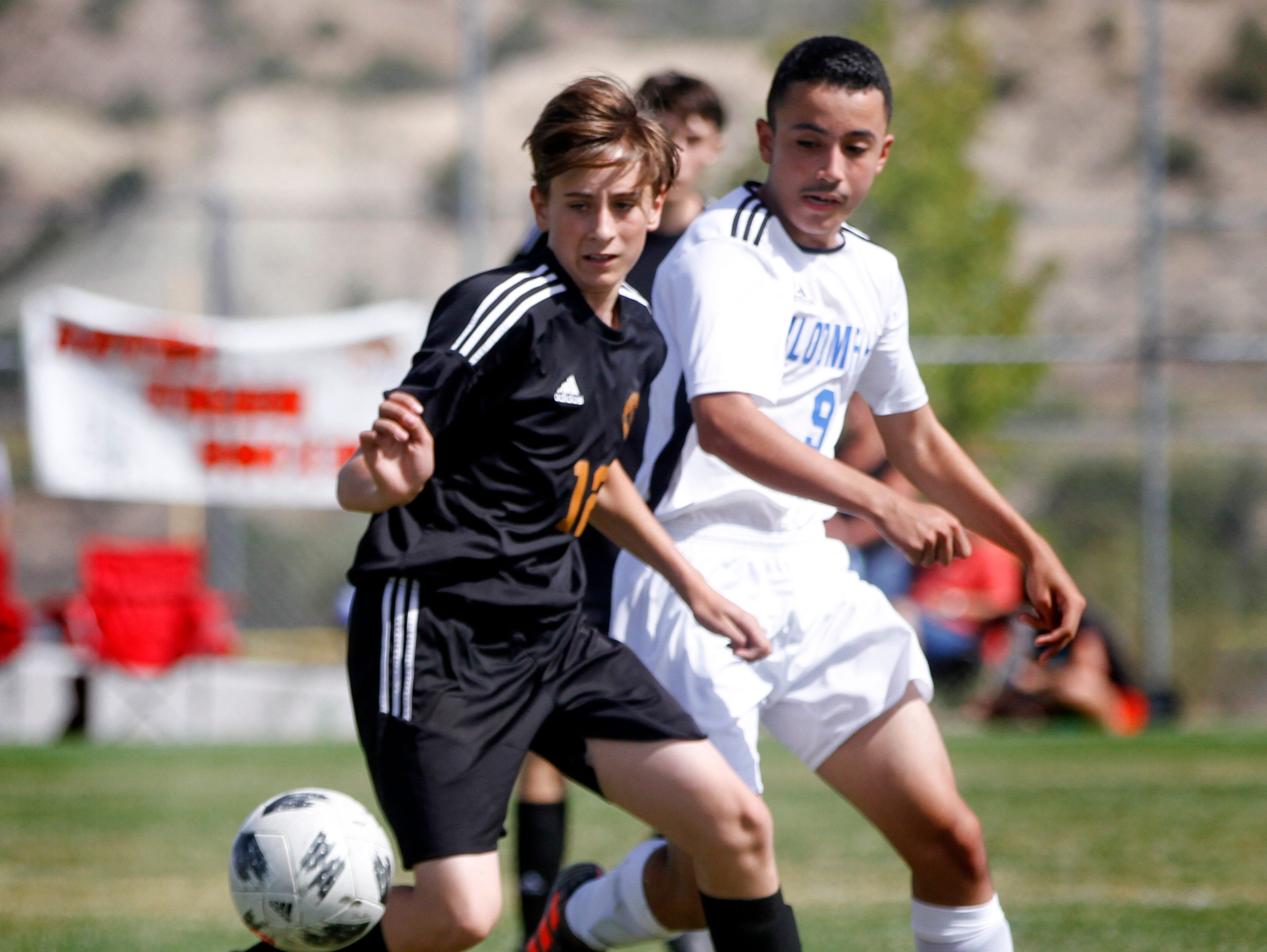 Aztec's Kolton Bruhn and Bloomfield's Jesus Jacquez chase the ball, Friday, Aug. 24, 2018 during their soccer game at the Aztec Tiger Soccer Complex.