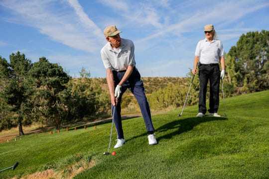 Mike Dushi eyes the fairway as unified partner Steve Cunningham watches Friday during the Special Olympics New Mexico Four Corners Invitational at the Pinon Hills Golf Course in Farmington.