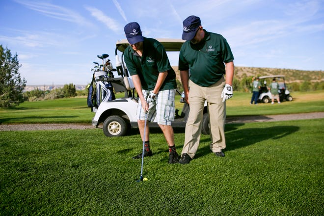Unified partner Scot Morin, right, helps his athlete Alex Correa with his footwork Friday during the Special Olympics New Mexico Four Corners Invitational at the Pinon Hills Golf Course in Farmington.