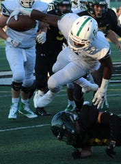 West Bloomfield's Donovan Edwards flies over a Groves defender.