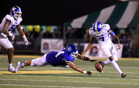 Detroit Catholic Central's Steven Kolcheff reaches for the ball as Walled Lake Western's Sam Johnson fumbles, but recovers during the second half.