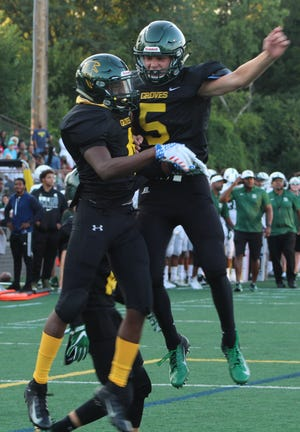 Senior wide receiver Khalil Dawsey (4) chest bumps with teammate Christian Thomas after scoring a second-quarter touchdown.