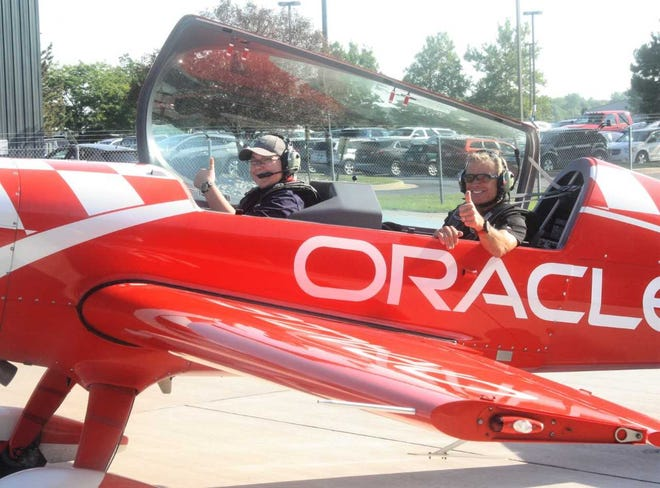 Westland teenager Buster Wurm (front) gives a thumbs-up along with stunt pilot Sean Tucker moments before the pair's 30-minute flight in the skies over southeast Michigan.